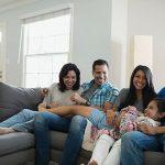 Smiling family relaxing on living room sofa